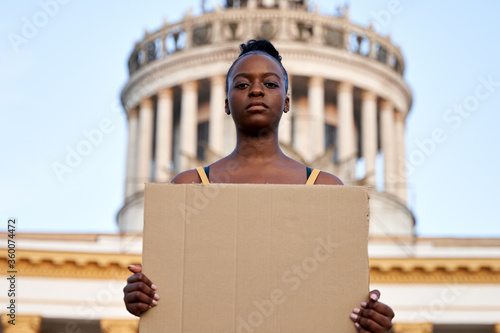 Photo Young african woman activist stand outdoor hold empty blank sign protesting on street