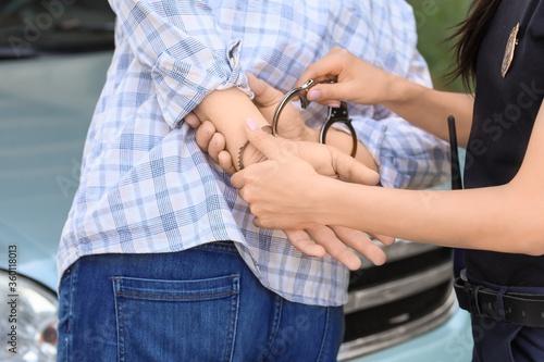 Obraz na plátně Police officer arresting criminal outdoors