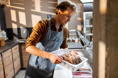 Photographie Portrait of a handsome seller working with ice cream at the counter of pastry sh