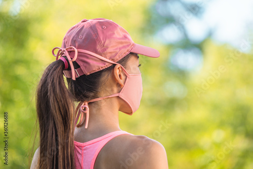 Corona virus face mask COVID-19 young healthy woman on outdoor walk wearing cloth string ties with pink sports cap. Summer lifestyle.