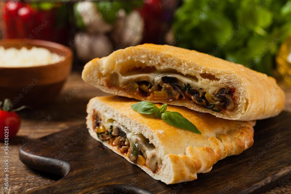 Fototapeta Italian calzone with mushrooms and ham.
