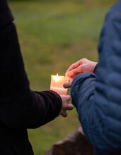 Grave Candle Being Lit By Two Persons.