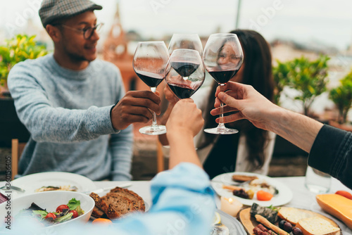 Photo Best friends making cheers with red wine glasses, Group of people having fun toa