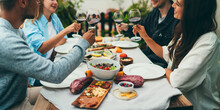 Multi Ethnic Group Of People Dining Out Smiling And Laughing, Friends Sitting At The Dinner Table Talking And Planning To Go On Summer Vacation Together In A Car With Tents, Friendship Celebration