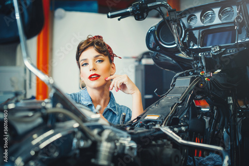 beautiful girl posing repairs a motorcycle in a workshop, pin-up style, service and sale
