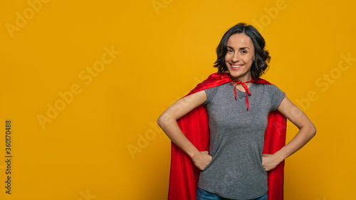 Fotografía I am a superwoman! A young, beautiful girl, standing confidently with her fists on her waist, wearing red superman cloak, smiling like a real hero, ready to accomplish any task in the world