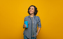 Relaxed Day. Half-length Photo Of A Relaxed  Smiley Girl In A Checkered Shirt, Holding A Blue Cup In Her Right Hand, Looking Aside And Up, Standing With Her Left Hand In A Pocket.