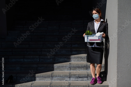 Fotografie, Obraz unemployed woman in a protective mask is standing with a box of personal belongings at the stairs