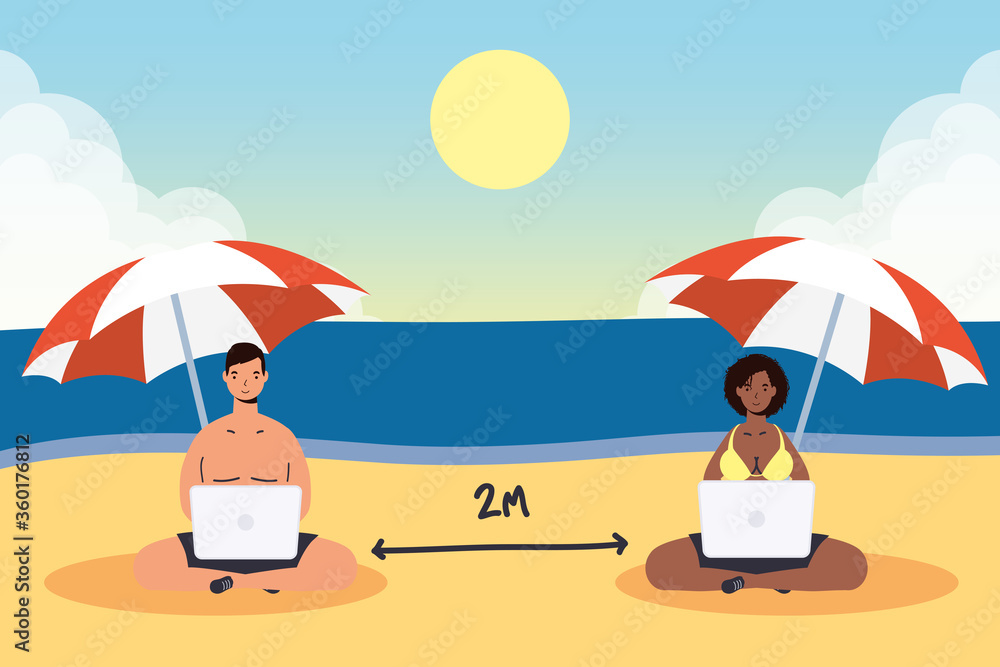 Fototapeta couple using laptop on the beach practicing social distancing scene ,summer time vacations