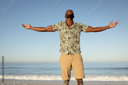 An African American man with his arms outstretched on beach on a sunny day