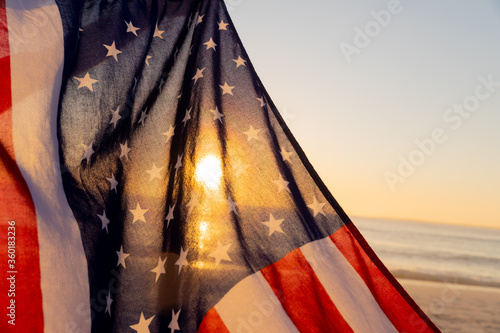 The sun seen through a US flag on a beach