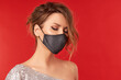Upset woman in trendy fashionable outfit during quarantine. Model dressed stylish protective face mask on red studio background
