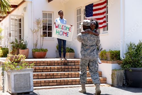 African American woman and her daughter standing  welcoming an African American soldier