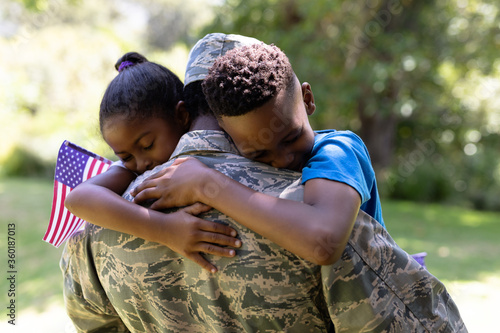 African American man wearing a military uniform holding his children