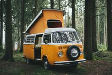 Orange Retro Bulli Vintage Camper In Green Forest.
