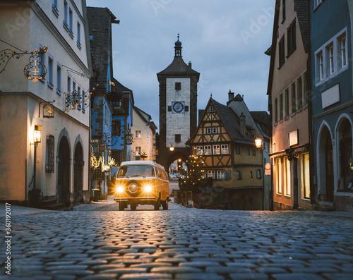 Obraz na plátně Orange Volkswagen Transporter T2 on background of Rothenburg ob der Tauber, Christmas decorated city of Franconia, Bavaria in Germany