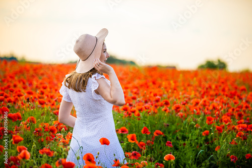 Papel de parede Woman with hat is standing in poppy field and enjoying a sunset, Czech republic