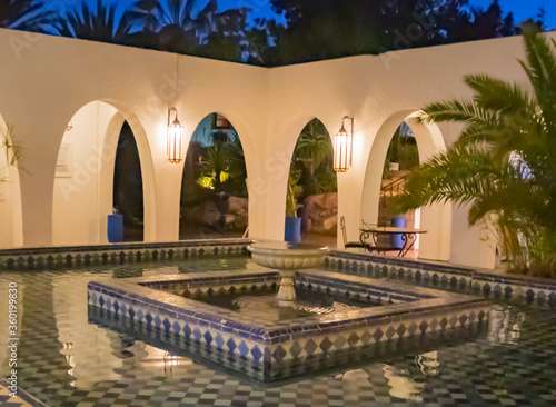 White and blue diamond-shaped tiles inlaid in fountain with white horseshoe arches behind with two lanterns during blue hour dusk in Agadir, Morocco Tapéta, Fotótapéta