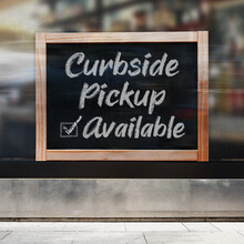 A Business Sign That Says 'Curbside Pickup Available' On The Window.