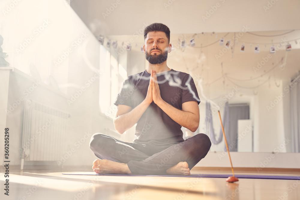 Fototapeta Serene young man meditating in yoga studio