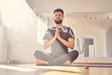Serene young man meditating in yoga studio