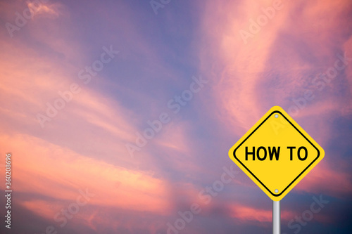 Photo Yellow color transportation sign with word how to on violet cloud sky background