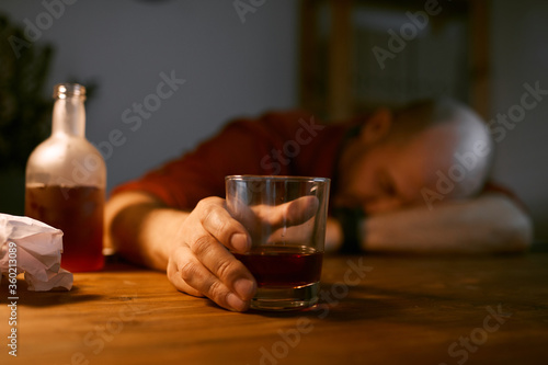 Photo Image of glass with alcohol on the table with drunk man sleeping in the backgrou