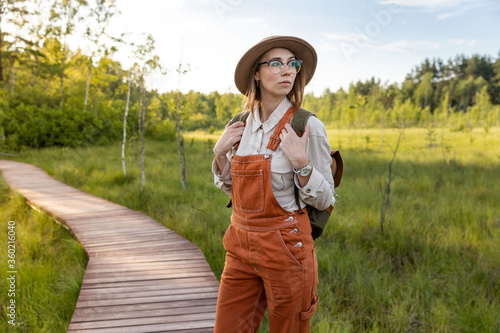 Fotografie, Obraz Portrait of woman botanist with backpack on ecological hiking trail in summer