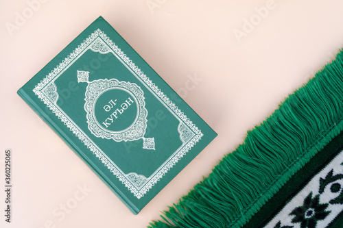 Fototapety, obrazy: Muslim islamic faith concept Koran book , green rosary, green mat pray . Neutral beige background. layout and Space for text. The inscription of the Quran in the Tatar language