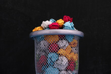 Crumpled Colorful Paper Balls In A Trash Can