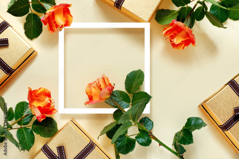 Fototapeta Beautiful yellow roses with golden gift box and white frame on delicate yellow paper background.  Valentine's Day Greeting Card. With place for your text.