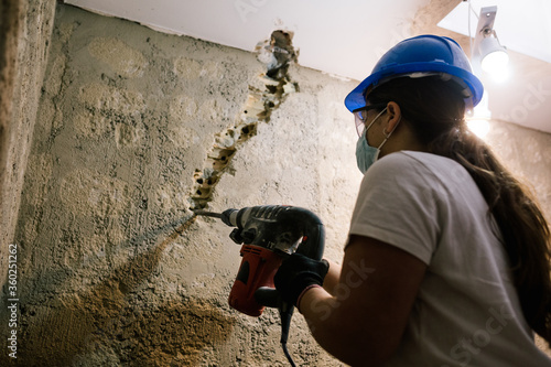 Fotomural woman working hard with a drill and with mask