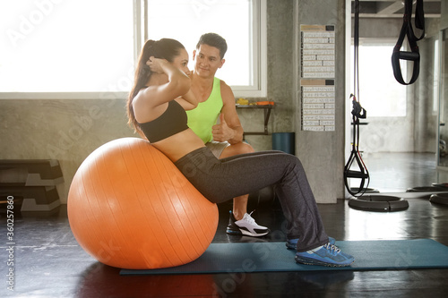 Fototapeta A Caucasian young fit woman working out with fitness ball and her muscular trainer at the gym obraz