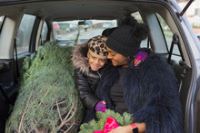 Portrait Happy Mother And Daughter In Car With Christmas Tree