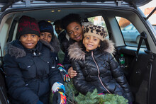 Portrait Happy Brothers And Sister With Christmas Tree In Back Of Car