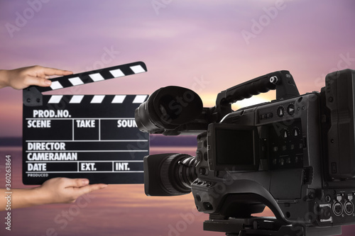 Valokuva Modern video camera and assistant with clapperboard outdoors, closeup