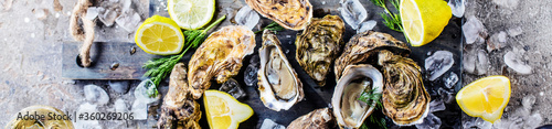 Fotografia top view of delicious oysters on ice cubes and wine glass
