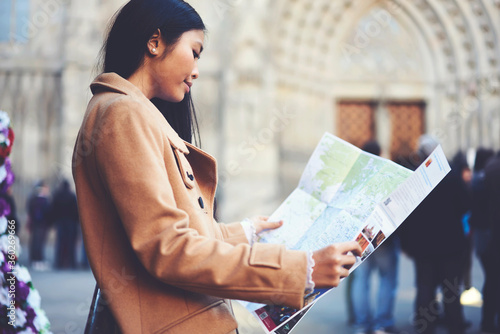 Obraz Attractive young female hipster in trendy spring coat fond of traveling spent short weekends in old european town using map to find tourist route to get to popular notable places in downtown - fototapety do salonu