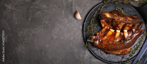 Slate plate with delicious roasted ribs and space for text on grey table, top view. Banner design