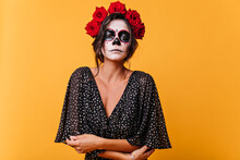 Sad Dead Bride With Zombie Makeup Standing On Yellow Background. Elegant Latin Woman With Roses In Hair Preparing For Halloween.