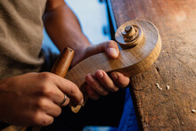 Cropped Faceless Craftsman Carving Swirl Of Violin Head While Working With Wooden Detail Using Bit At Table In Workshop
