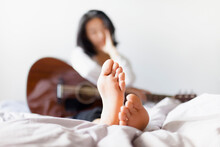 Woman With Bare Feet Holding G...