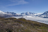 Full length of hiker looking at glacier against blue sky, Knik Glacier, Palmer, Alaska