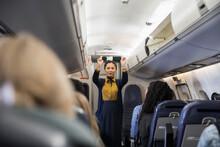 Flight Attendant Demonstrating Seat Belt Safety In Airplane