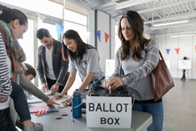 Woman Placing Ballot In Ballot Box At American Polling Place