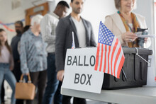 Ballot Box With American Flags On Table In Polling Place