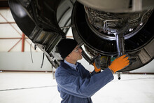 Mechanic Inspecting Airplane E...