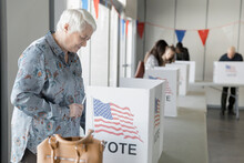 Senior Woman Voting In Voting Booth At American Polling Place
