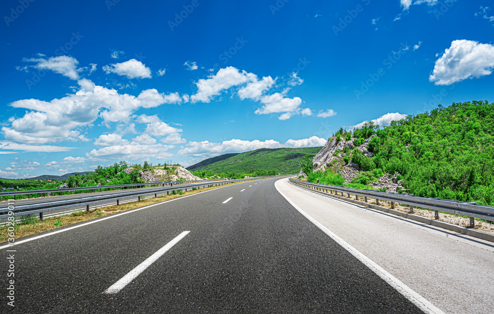 Fototapeta Mountain highway with blue sky and rocky mountains on a background