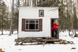 Young woman leaving cabin in woods in snow